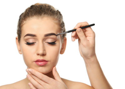 Young woman undergoing eyebrow correction procedure on white bac